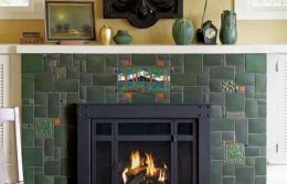 Green Motawi industry tiles are along with landscape and other ornamental tiles in a seemingly random design on this fireplace.