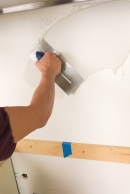 man coating a wall with thinset while preparing to put in a glass mosaic backsplash