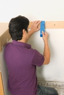 man establishing a center range regarding wall while preparing to put in a cup mosaic backsplash