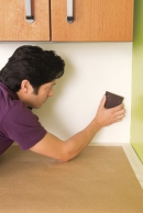 man planning the wall surface to install a glass mosaic backsplash