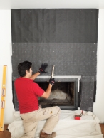 man securing metal lath over the felt of a hearth to generate a rock veneer surround