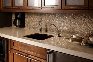 Photo features One Quartz Micro Flecks in Cancun seashore regarding the countertop with Glass Pebbles in Wheat from the backsplash.