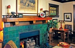 beautiful green tile accented by riveted iron straps makes the hearth the centerpiece associated with room in this Memphis bungalow. It's hard to believe a previous owner had coated the entire thing red.