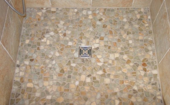Applying stone tile to shower floor