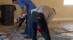 Workers remove porcelain tile